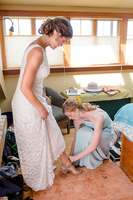 putting on the wedding shoes for the bride