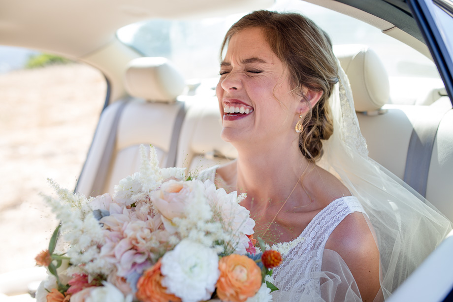 bride laughing in the car before wedding ceremony