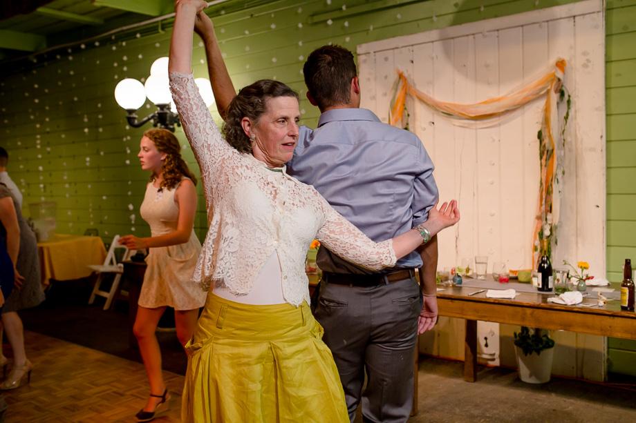 wedding guest dancing in yellow dress