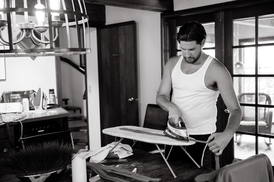 groomsman ironing his wedding tie