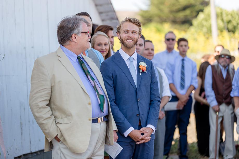 groom getting emotional watching his bride walking down the path
